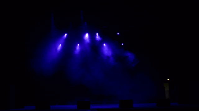 Few-colored-spotlights-in-the-dark-on-stage-
