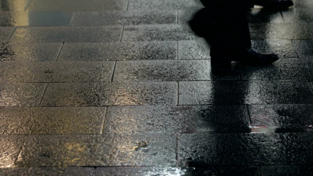 Slow-motion-view-of-raindrops-and-footsteps-of-pedestrians-on-a-sidewalk-