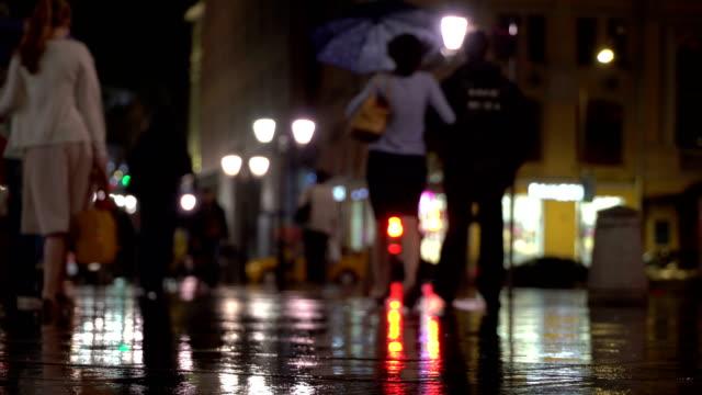 Resumen-tarde-lluviosa-de-fondo-en-la-ciudad-en-tonos-oscuros-naturale-Las-gotas-de-lluvia-caen-sobre-el-asfalto-colorido-iluminado-por-farolas-Entre-la-multitud-de-peatones-van-a-dos-amigos-bajo-paraguas-y-hablar-Estilo-de-vida-de-la-ciudad-moderna