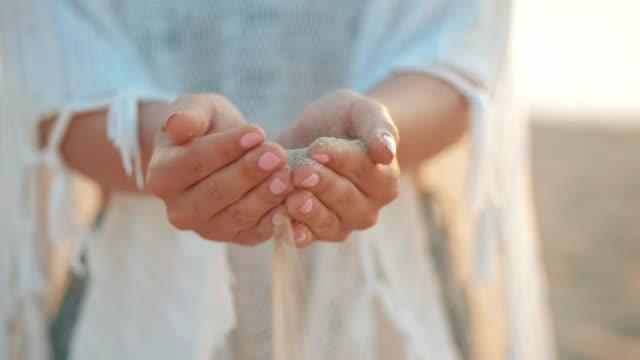 Nahaufnahme-von-Frau-Gießen-Sand-durch-die-Finger-am-Strand-laufen-Hand-einer-Frau-in-weißer-Kleidung-nieselte-Meer-Sand-durch-ihre-Finger-vor-einer-Kulisse-von-Meer-Konzeptbild