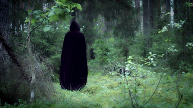 4K-Halloween-Horror-hombre-con-cabo-negro-caminando-en-bosque