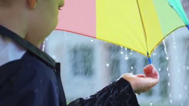 Chico-con-paraguas-captura-las-gotas-de-lluvia