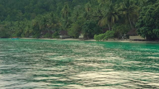 Tropical-rain-over-the-bamboo-homestay-huts-on-the-beach-Gam-Island-Raja-Ampat-West-Papua-Indonesia