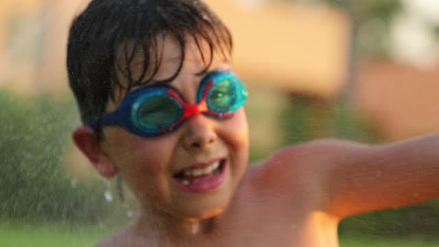Niño-feliz-sonriendo-a-la-cámara-mientras-se-rocía-con-chispitas-de-agua-en-resolución-4k-de-60fps-Infantil-buscando-positivo-sonriendo-a-la-cámara-durante-el-atardecer-de-verano-vacaciones-vacaciones-4k-mov