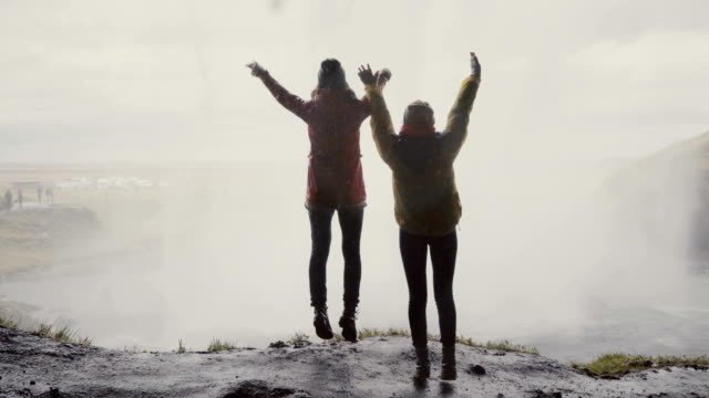 Back-view-of-two-happy-female-tourists-near-the-Gljufrabui-waterfall-in-Iceland-Women-jumping-of-joy-near-sight