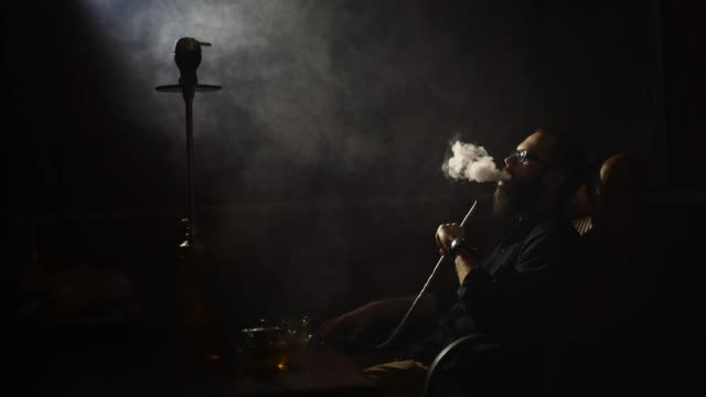 young-bearded-man-in-glasses-smokes-a-hookah-and-blow-out-smoke-closeup-on-black-background-in-slow-motion-in-4k