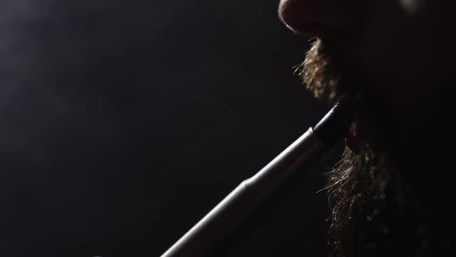 hombre-barbudo-joven-en-gafas-fuma-un-narguile-y-sople-closeup-humo-sobre-fondo-negro-en-cámara-lenta-en-4k