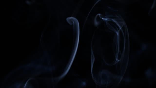 humo-flotando-lentamente-a-través-del-espacio-sobre-fondo-negro-