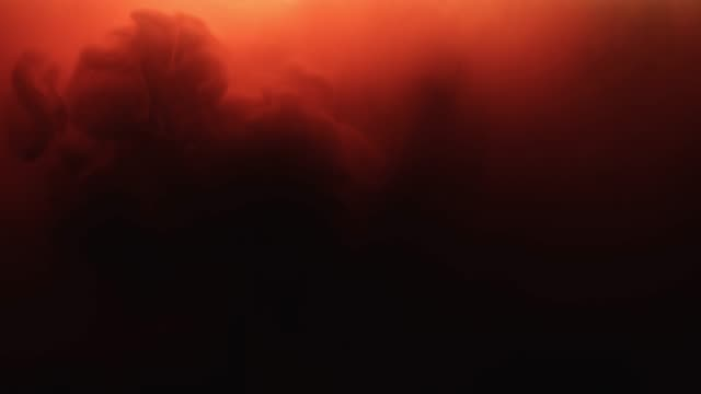 Tinta-roja-que-fluye-en-el-agua-sobre-fondo-negro-