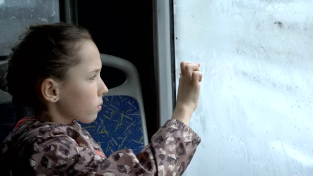 A-little-girl-sits-in-the-bus-in-the-back-seat-and-draws-pictures-with-her-finger-on-the-wet-misted-glass-Outside-the-window-drive-cars-Portrait-