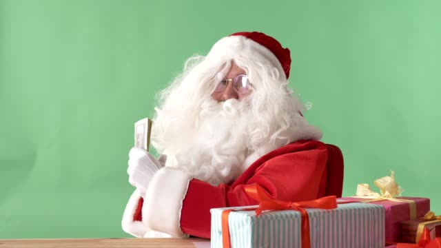 Satisfied-Santa-Claus-holds-dollars-money-and-shows-a-liking-sign-chromakey-in-the-background