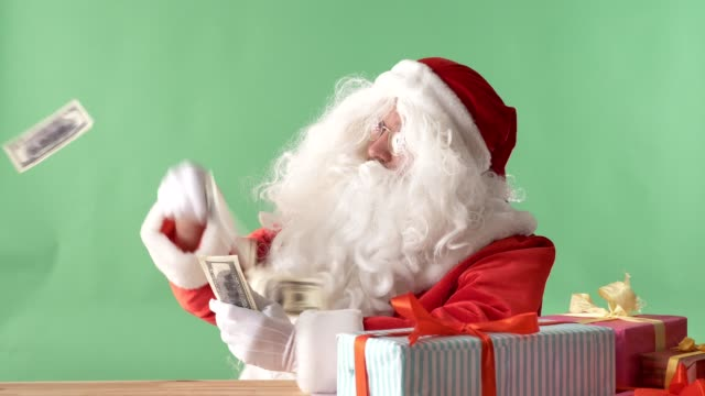 Satisfied-Santa-Claus-throwing-bills-out-of-a-bundle-money-on-table-money-on-table-chromakey-in-the-background