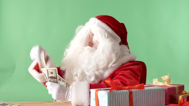 Satisfied-Santa-Claus-throwing-bills-out-of-a-bundle-money-on-table-money-concept-chromakey-in-the-background