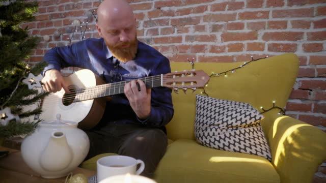 Hombre-tocando-la-guitarra-junto-al-árbol-de-Navidad