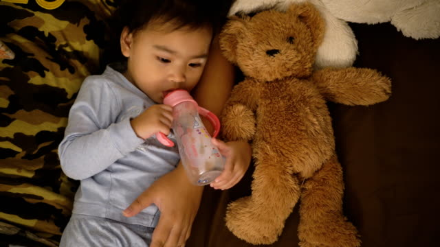 Asian-girl-eating-milk-with-a-bottle-Hold-teddy-bear