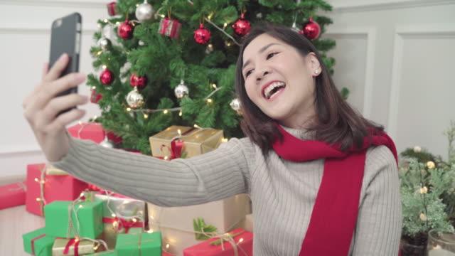 Alegre-feliz-joven-mujer-asiática-con-smartphone-selfie-de-Navidad-árbol-decorar-su-sala-de-estar-en-el-país-en-el-Festival-de-Navidad-Mujer-de-estilo-de-vida-celebrar-Navidad-y-año-nuevo-concepto-