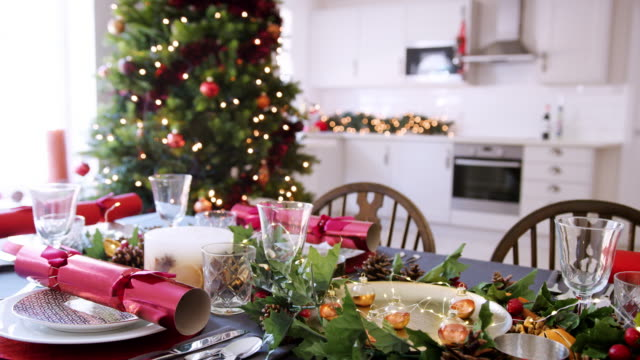 A-dining-table-prepared-for-Christmas-dinner-with-a-Christmas-tree-and-kitchen-background-bokeh