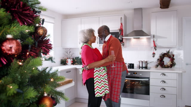 Happy-mature-black-couple-holding-champagne-glasses-laughing-and-dancing-in-the-kitchen-while-preparing-Christmas-dinner-side-view