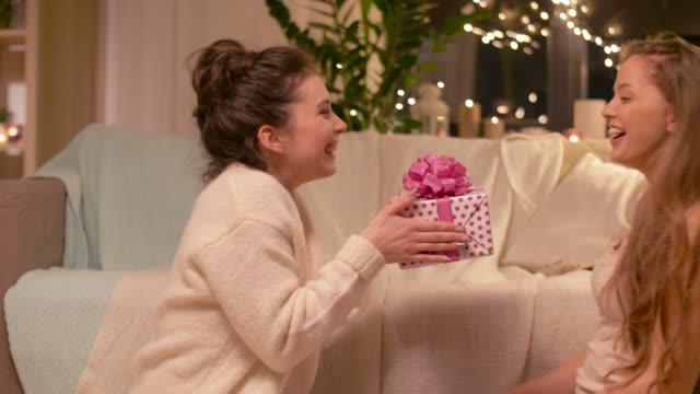 amigas-felizes-con-el-regalo-de-la-Navidad-en-casa