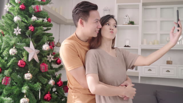 Pareja-asiática-con-smartphone-selfie-de-árbol-de-Navidad-decora-su-sala-de-estar-en-el-país-en-el-Festival-de-Navidad-Estilo-de-vida-mujer-y-hombre-feliz-verano-celebran-Navidad-y-año-nuevo-concepto-