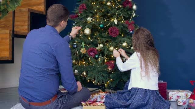 Glückliche-Familie-schmücken-Weihnachtsbaum-zu-Hause