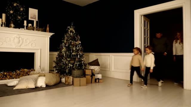 Feliz-familia-paseos-en-la-sala-de-estar-para-ver-los-regalos-bajo-el-árbol-de-Navidad