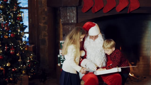 Santa-Claus-is-showing-an-album-with-photos-to-kids-on-the-background-of-a-fireplace-with-Christmas-socks-and-with-a-Christmas-tree-in-the-room-but-the-boy-in-a-plaid-shirt-runs-away-