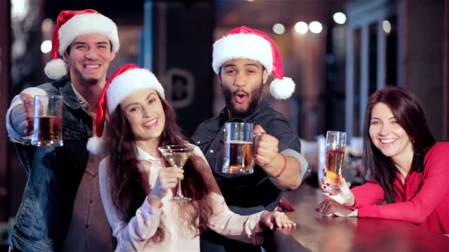 Three-friends-in-Santa-hats-and-the-girl-behind-the-bar-with-a-glass-of-beer