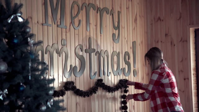 Young-woman-putting-up-Christmas-decorations