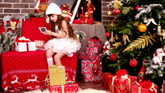 little-girl-lays-out-the-name-cards-on-Christmas-gifts