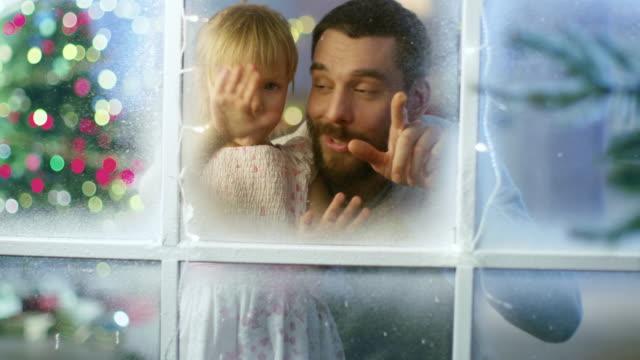 En-Nochebuena-padre-y-su-linda-hija-mira-a-través-de-la-Nevada-ventana-congelada-y-sonreír-