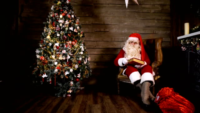 Santa-Claus-pulling-out-Reading-Book-near-Christmas-Tree-at-Home