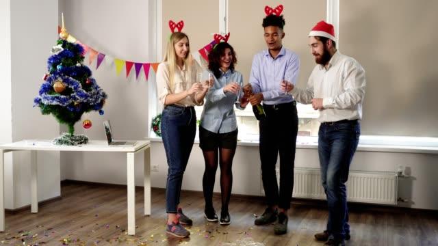 Atractivo-joven-oficinistas-abriendo-una-botella-de-vino-espumoso-celebrando-Navidad-y-año-nuevo-en-la-oficina-Compañeros-felizes-celebrando-en-la-oficina