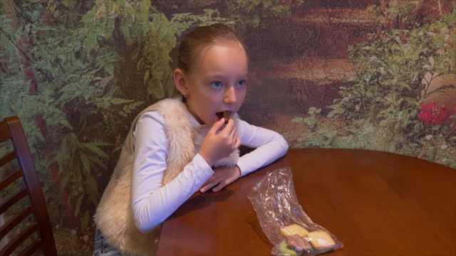 Young-caucasian-girl-sitting-at-table-Young-white-girl-eating-gingerbread-ginger-cookies-and-watching-TV-Young-take-breakfast-at-home-kitchen-Christmas-breakfast-Looking-to-camera-