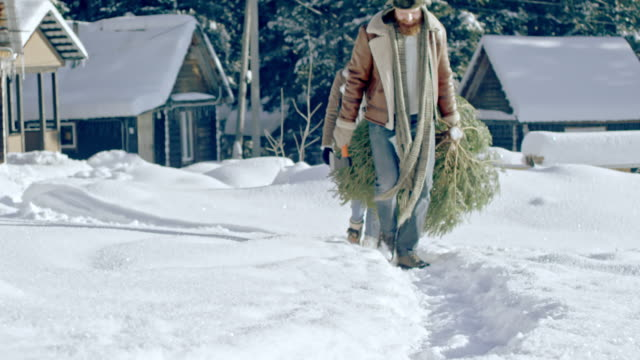 Family-Carrying-Wild-Christmas-Tree-Home