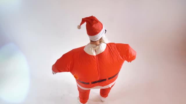 Un-artista-en-un-traje-de-Santa-inflable-saluda-al-espectador-