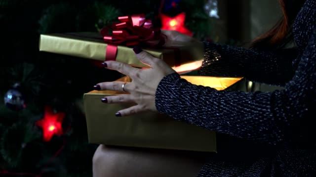 La-chica-abre-un-regalo-junto-al-árbol-de-Navidad-