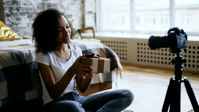 Attractive-african-girl-recording-video-blog-about-packing-christmas-gift-box-at-home