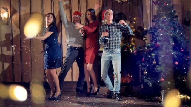 Four-friends-dance-and-sing-near-a-Christmas-tree-
