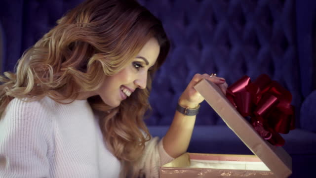 Young-attractive-woman-with-beautiful-curly-hair-opens-a-glowing-gift-box