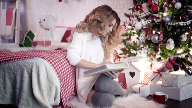 Xmas:-young-attractive-woman-view-photo-album-near-Christmas-tree