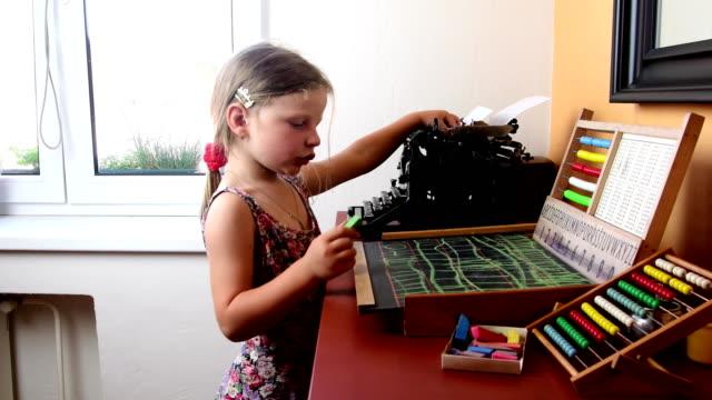 Süßes-kleines-Mädchen-spielt-mit-Abakus-und-schreibt-an-die-Tafel-mit-Kreide-Vorschule-Konzept-Kindheit-Spielzeug-Abakus-mit-tschechischen-Alphabet-und-Vintage-Schreibmaschine-Niedliche-Mädchen-wie-Vorschulkind