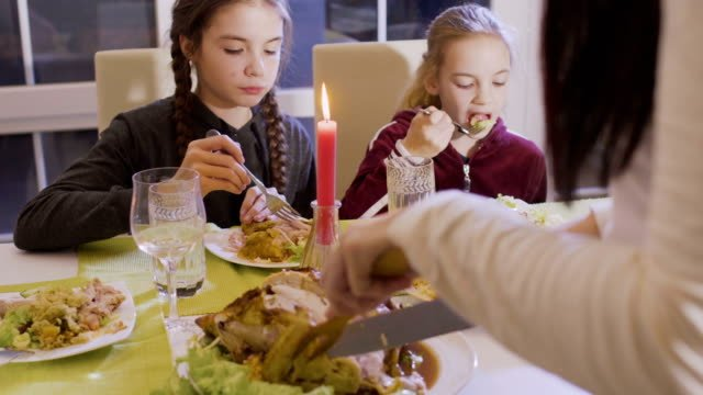 Woman-cuts-fried-chicken-at-the-festive-table