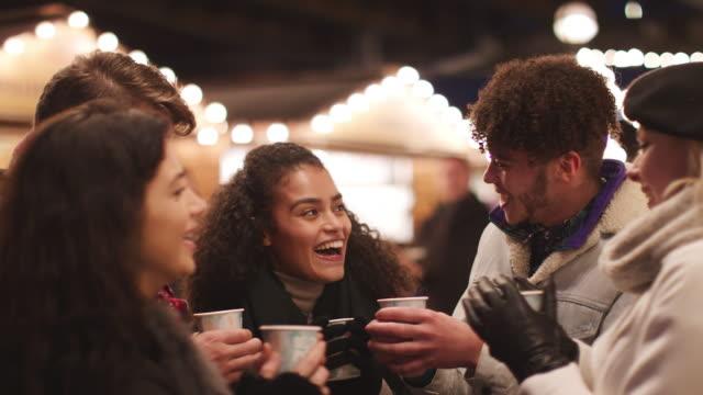 Gruppe-von-Freunden-trinken-Glühwein-am-Weihnachtsmarkt