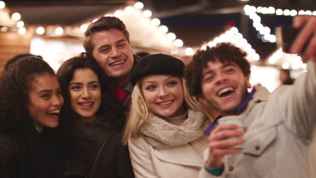 Young-Friends-Posing-For-Selfie-At-Christmas-Market