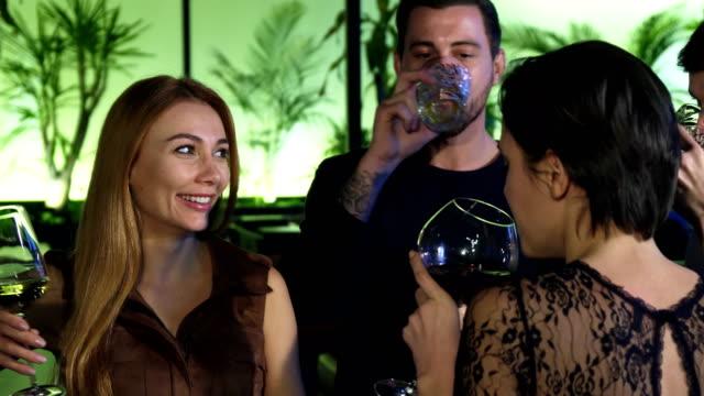 Gruppe-junger-Leute-genießen-trinken-zusammen-an-der-Bar-am-Abend