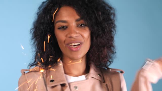 Brillante-fuego-de-Bengala-en-la-mano-de-la-mujer-afroamericana-sobre-fondo-azul-Concepto-de-vacaciones-de-Navidad-Joven-bonita-a-chica-con-peinado-afro-celebrando-sonriendo-disfrutando-4k