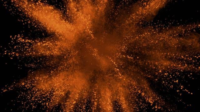 Orange-powder-exploding-on-black-background-in-super-slow-motion