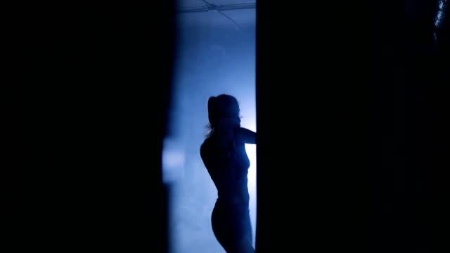 Silhouetten-von-Frau-Boxer-trainiert-in-dunklen-Turnhalle