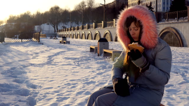 Young-woman-eats-a-burger-on-winter-street